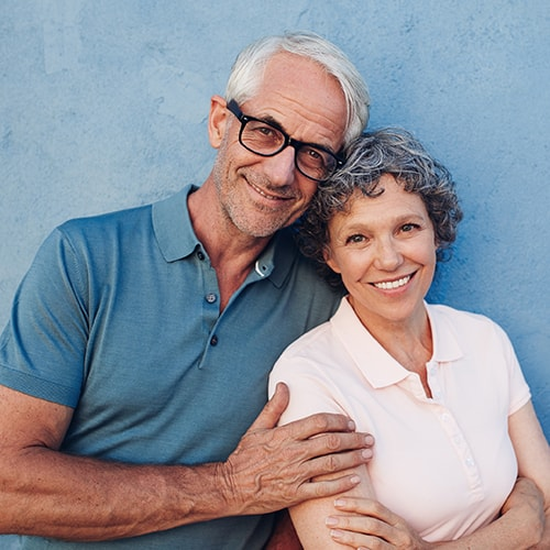 Smiling husband and wife after getting dental implants